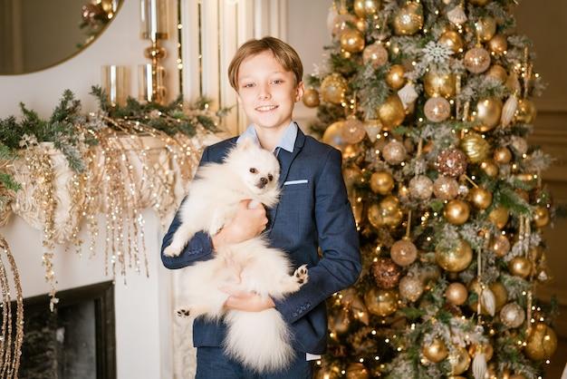 Hübscher kleiner blonder junge mit jungenhaar, fröhlich lächelndes gesicht im blauen anzug, spielt mit einem po...