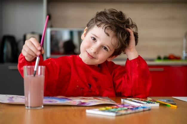 Hübscher kleiner junge, der bilder zu hause zeichnet