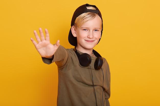 Hübscher kleiner junge, der isoliert über gelbem zeigen steht und mit den fingern nummer fünf nach oben zeigt, während er lächelt