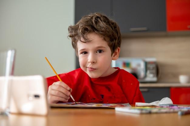 Hübscher kleiner junge, der zu hause fernunterricht zeichnet