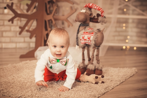 Hübscher kleiner junge unter weihnachtsdekorationen