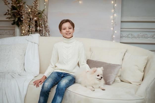 Hübscher kleiner kaukasischer junge auf dem sofa mit weißem hund auf hellem weihnachtshintergrund fröhliche chris...