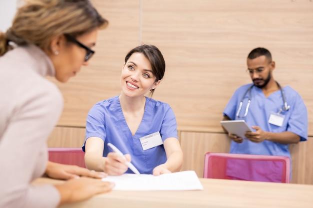 Hübscher kliniker in der uniform, die den patienten anlächelt, während er auf medizinisches dokument zeigt und junge frau konsultiert