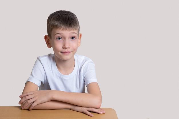 Hübscher kluger lächelnder junge, der am tisch sitzt und sich auf eine helle wand freut, kopieren raum. heimschulkonzept, schulanfang, fernunterricht
