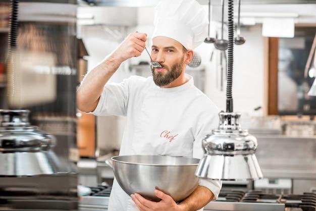 Hübscher koch kocht verkostung mit löffelessen in der schönen restaurantküche