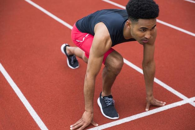 Hübscher konzentrierter afrikanischer athletenmann, der bereit ist zu beginnen