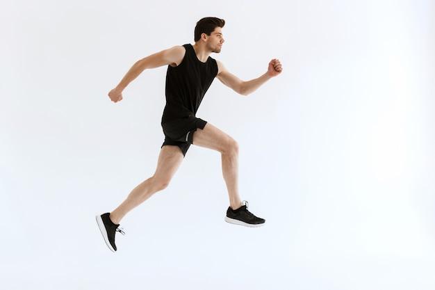 Hübscher konzentrierter junger starker sportmann, der läuft und.