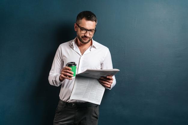 Hübscher konzentrierter mann, der kaffee liest zeitung liest.