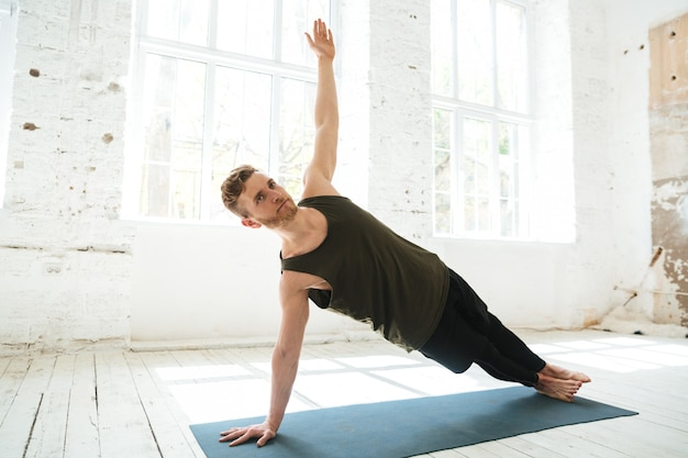 Hübscher konzentrierter mann, der yoga auf matte tut