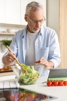 Hübscher konzentrierter reifer mann, der salat mit tablette kocht