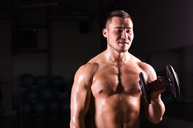 Hübscher kraftsportler mit hantel. starker bodybuilder mit sixpack, perfekter bauchmuskulatur, schultern