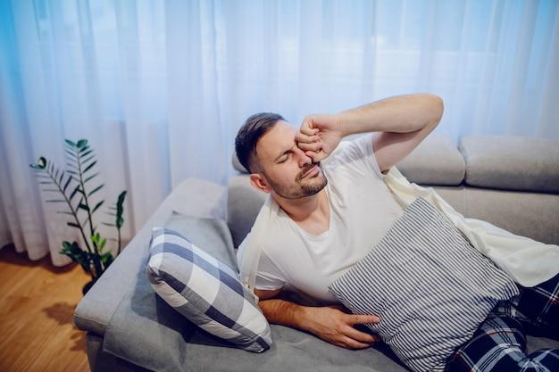 Hübscher kranker kaukasischer mann im schlafanzug, der nach mittagsschläfchen aufwacht.