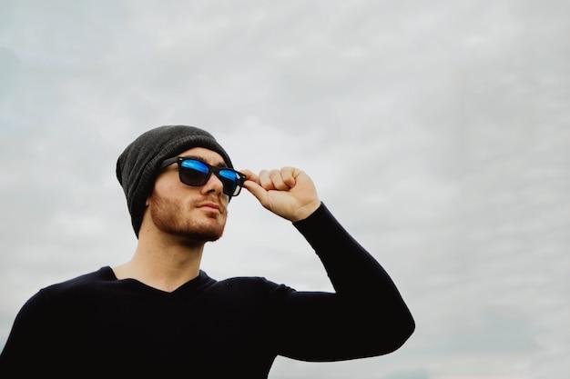 Hübscher kühler junger mann mit sonnenbrille