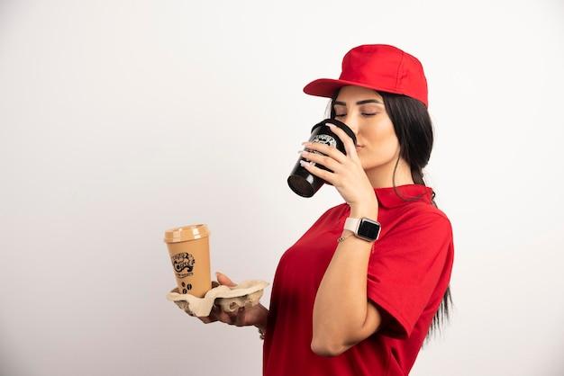 Hübscher kurier, der frischen kaffee trinkt. hochwertiges foto