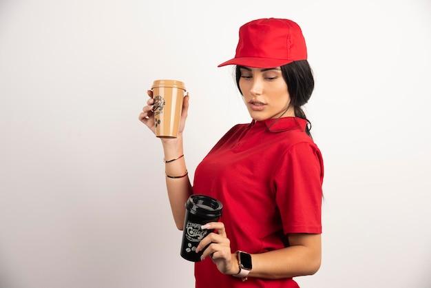 Hübscher kurier, der kaffeetassen auf weißem hintergrund hält. hochwertiges foto