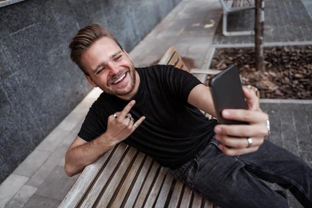 Hübscher lachender junger blonder mann, der selfie macht oder live auf dem smartphone streamt und auf der bank auf der straße gestikuliert, trägt schwarze jeans und ein schwarzes t-shirt