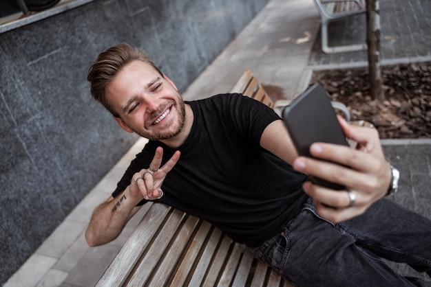 Hübscher lachender junger blonder mann, der selfie macht oder live auf dem smartphone streamt und ein friedenszeichen gestikuliert, während er auf der bank auf der straße sitzt, trägt schwarze jeans und schwarzes t-shirt