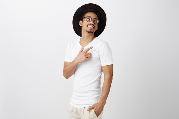 Hübscher lächelnder afroamerikanermann, der obere rechte ecke zeigt, zufrieden, produkt wählend