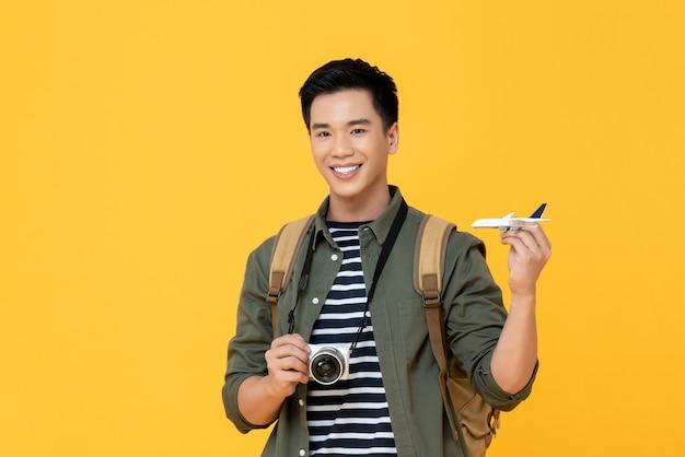 Hübscher lächelnder asiatischer touristenmann, der flugzeugmodell und kamera hält