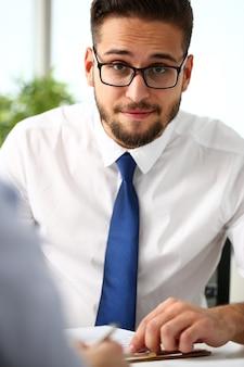 Hübscher lächelnder bärtiger angestellter am büroarbeitsplatz mit silbernem stift in den armen tun papierkramporträt. personal dress code worker jobangebot kundenbesuch studienberuf chef marktidee coach training