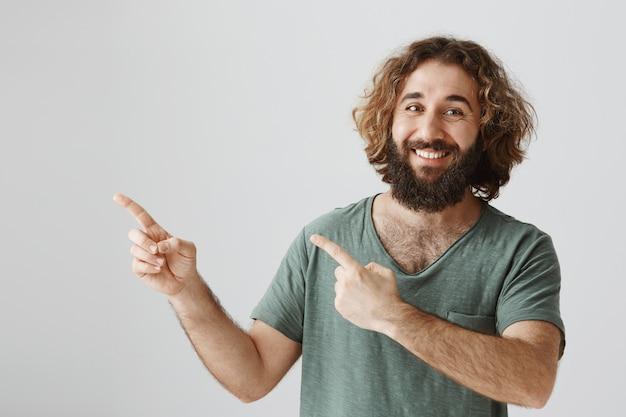 Hübscher lächelnder bärtiger arabischer kerl, der obere linke ecke zeigt, machen ankündigung