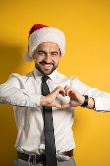 Hübscher lächelnder bärtiger mann in der weihnachtsmannmütze, die geste lokalisiert auf gelbem hintergrund zeigt. glücklich lächelnder angestellter oder manager setzt eine weihnachtsmütze auf und ist bereit, den angestellten zu gratulieren.