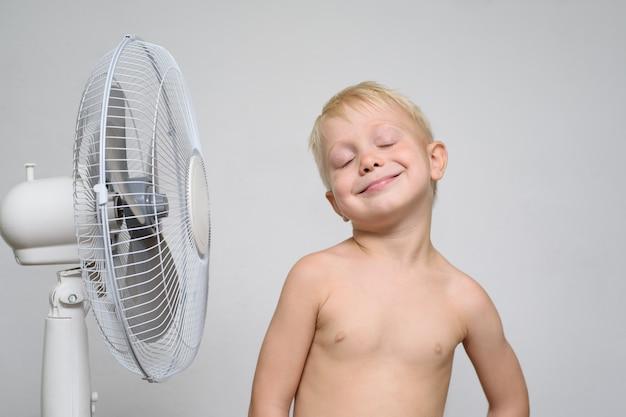 Hübscher lächelnder blonder junge mit dem nackten torso und den geschlossenen augen steht nahe einem ventilator. sommer-konzept