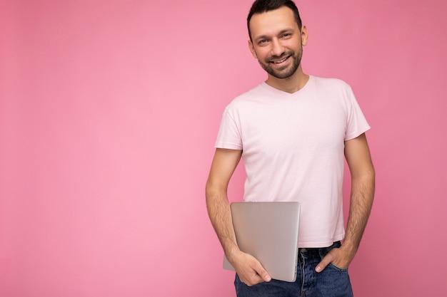 Hübscher lächelnder brunet-mann, der laptop-computer hält, der kamera betrachtet