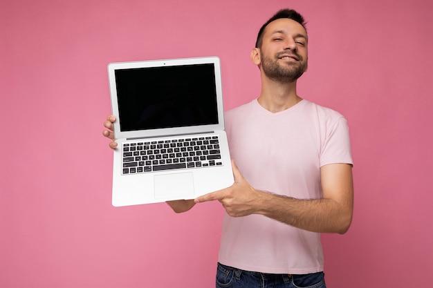 Hübscher lächelnder brunet-mann, der laptop-computer hält und kamera im t-shirt auf lokalisiertem rosa hintergrund betrachtet.
