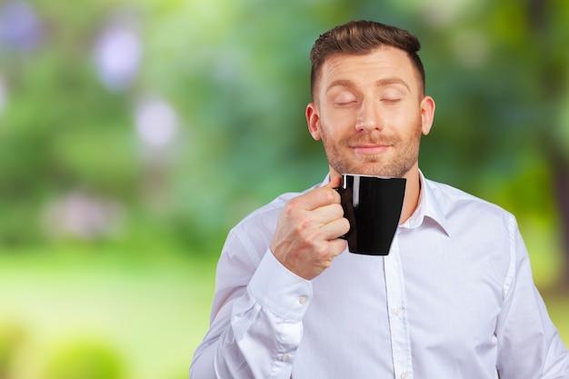 Hübscher lächelnder geschäftsmann holding cup