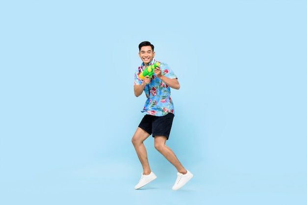 Hübscher lächelnder junger asiatischer mann, der mit wasserpistole spielt und für songkran festival in thailand und südostasien springt
