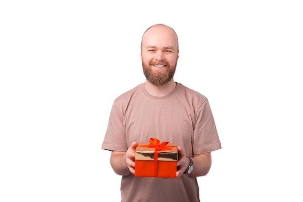 Hübscher lächelnder junger bärtiger mann, der geschenkbox auf weiß hält