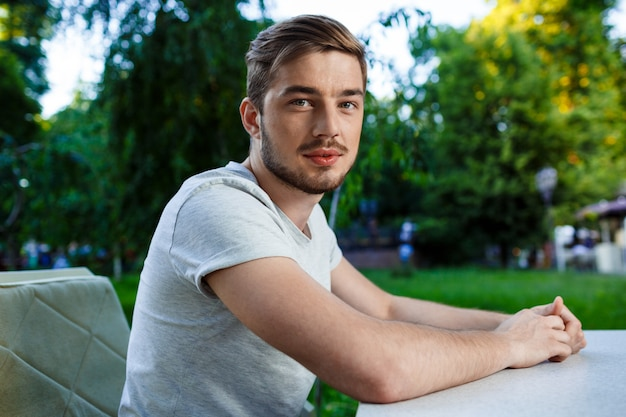 Hübscher lächelnder junger mann, der am tisch im open-air-café sitzt