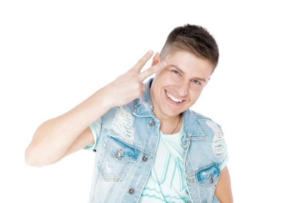 Hübscher lächelnder junger mann im denim, der geste nummer zwei lokalisiert zeigt