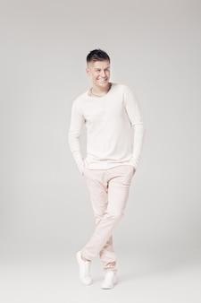 Hübscher lächelnder junger mann in einem weißen pullover und in den hosen auf einem weißen hintergrund