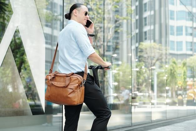 Hübscher lächelnder junger unternehmer, der auf roller mit ledertasche steht und am telefon anruft