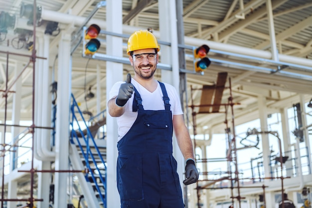Hübscher lächelnder kaukasischer arbeiter in overalls und mit helm auf kopf, der daumen hoch zeigt, während er an der raffinerie steht.