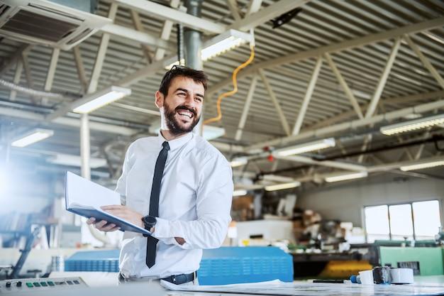 Hübscher lächelnder kaukasischer bärtiger grafikingenieur, der notizbuch beim stehen in der druckerei hält