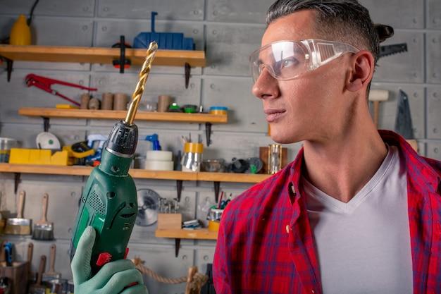Hübscher lächelnder kaukasischer junger mann im karierten hemd, sicherheitsbrille zum schutz, handschuhe, die mit bohrmaschine bohren, arbeiten in der tischlerei
