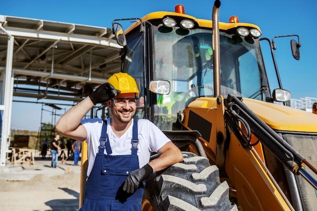 Hübscher lächelnder kaukasischer unrasierter arbeiter, der sich insgesamt auf lkw stützt und arme verschränkt hält. gewöhnlicher tag in der raffinerie.