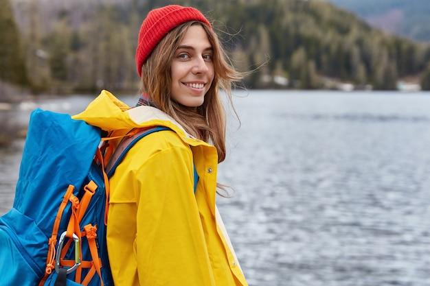 Hübscher lächelnder kaukasischer weiblicher reisender trägt rucksack