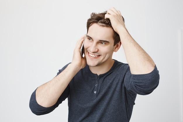 Hübscher lächelnder mann, der am telefon spricht und hand durch haare laufen lässt