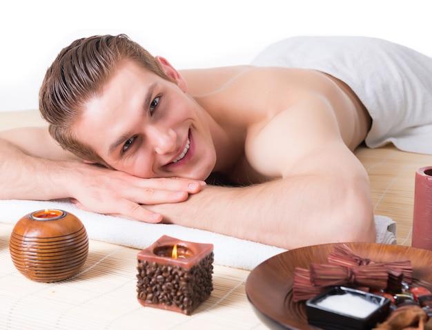 Hübscher lächelnder mann, der auf den massagetischen im spa-salon liegt und sich entspannt. schönheitsbehandlungskonzept.