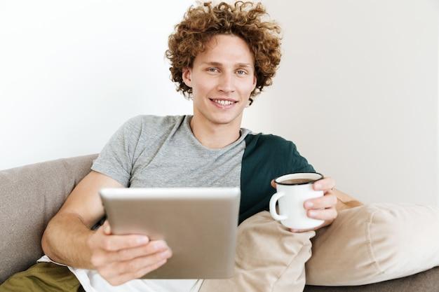 Hübscher lächelnder mann, der auf sofa unter verwendung des tablet-computers sitzt