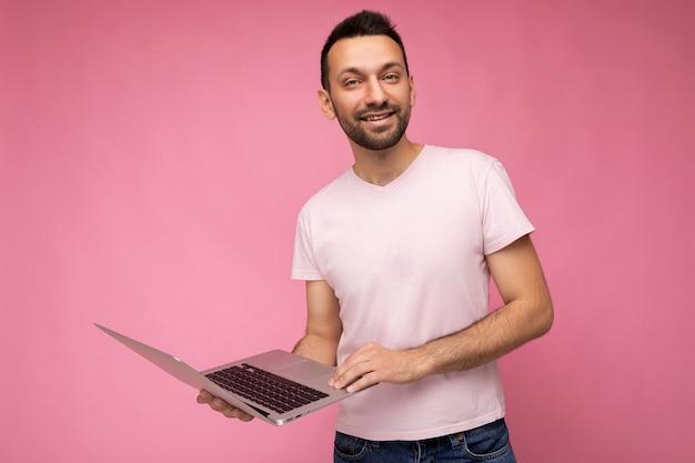 Hübscher lächelnder mann, der laptop-computer hält und kamera im t-shirt betrachtet