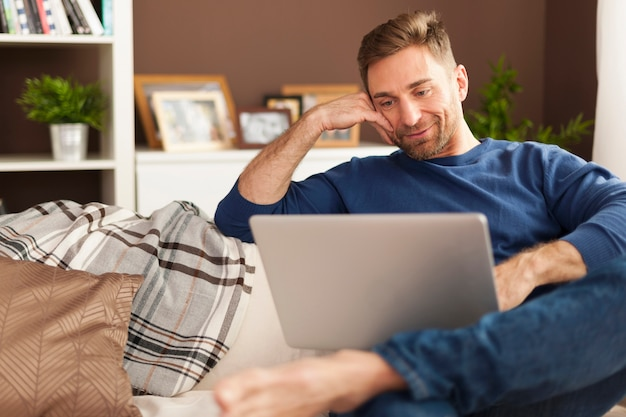 Hübscher lächelnder mann, der mit laptop zu hause entspannt