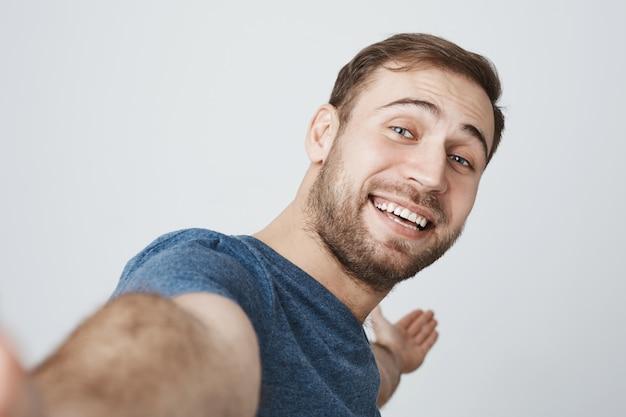 Hübscher lächelnder mann, der selfie nimmt