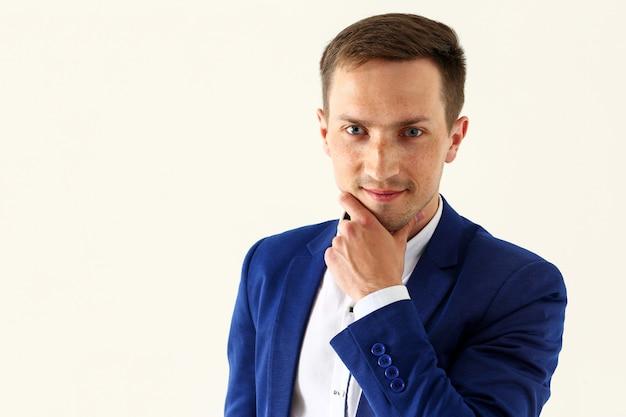 Hübscher lächelnder mann im anzug, der in kamera schaut