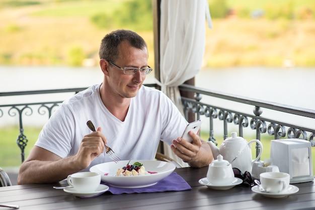 Hübscher lächelnder mann im café, der kuchen pavlova isst