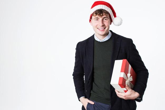 Hübscher lächelnder mann im weihnachtsmannhut